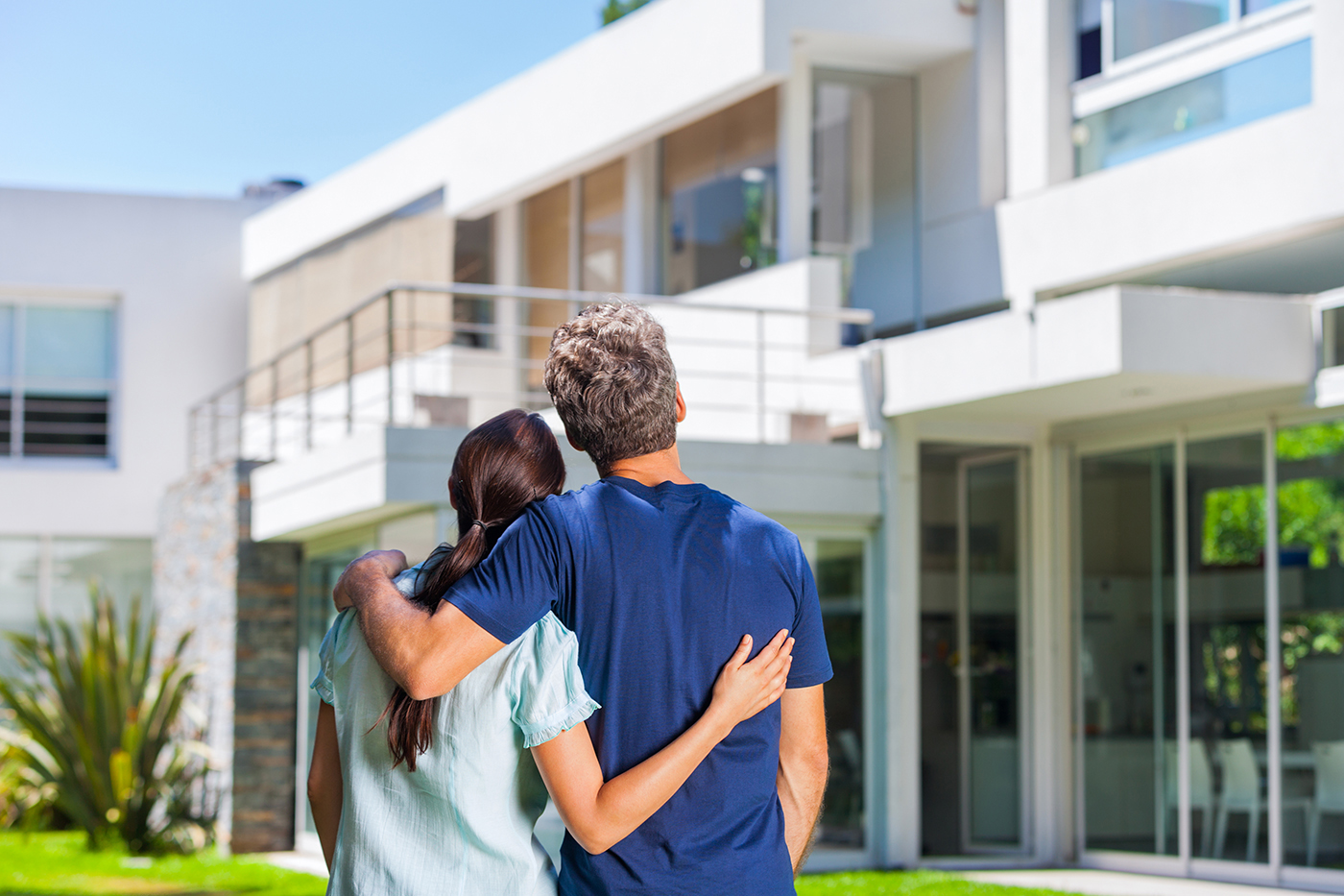 Couple in front of their new house after thorough home inspection services were provided