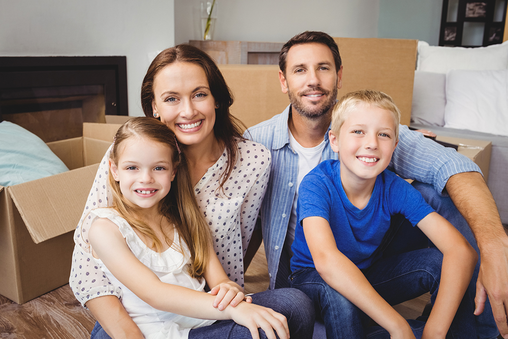 Portrait of smiling family with cardboard moving boxes in their new house after being reviewed by our home inspectors