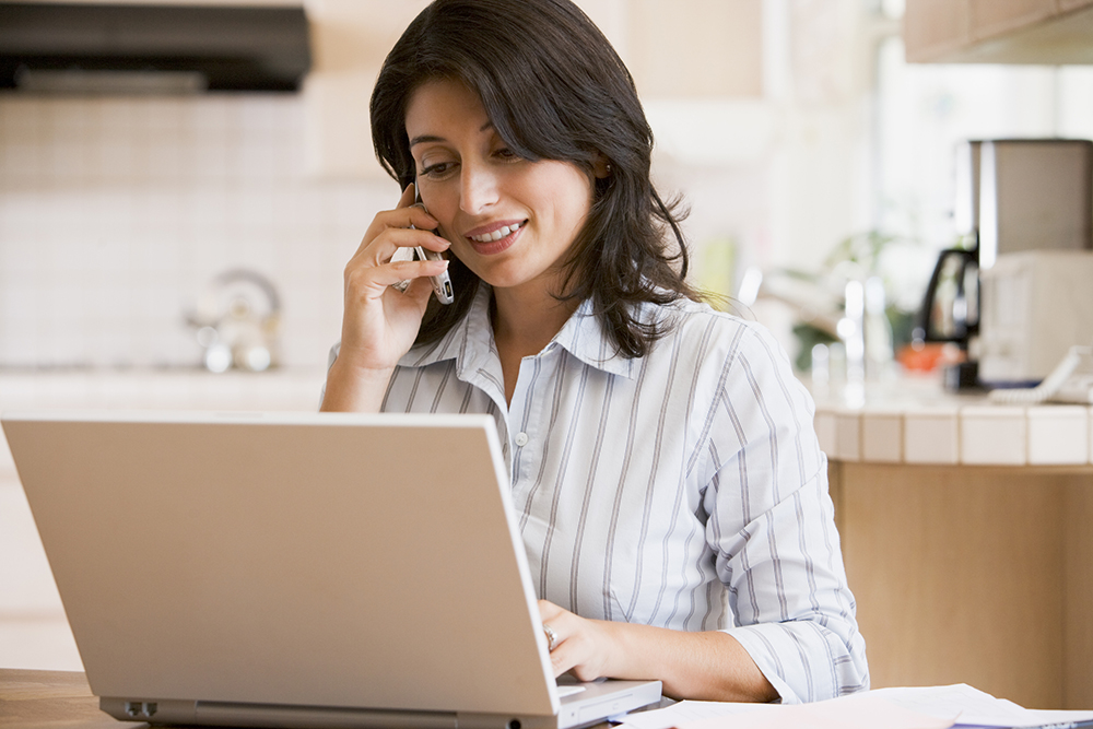 Woman in kitchen with laptop talking on the phone with our home inspectors
